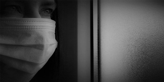 Zoom on the face of a person with a mask, who is looking at the room. The picture is black and white, giving a taste of being a patient at home during the pandemic.